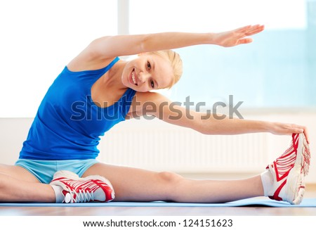 Smiling woman with high body flexibility exercising in the gym - stock photo