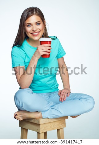 Smiling woman with long hair sitting on chair with coffee cup. Isolated. - stock photo