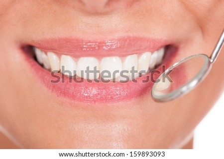 Smiling woman with perfect white teeth and a small dentists mirror reflecting her teeth being held alongside - stock photo