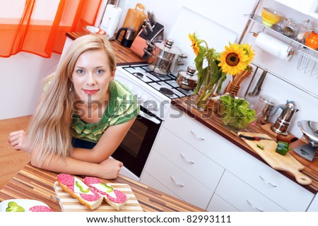 Smiling woman with sandwiches in the kitchen - stock photo