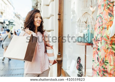 Smiling woman with shopping bag looking at boutique showcase - stock photo
