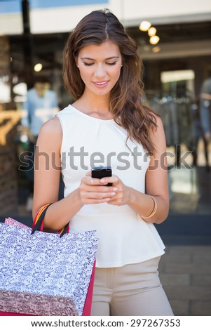 Smiling woman with shopping bags using smartphone at the shopping mall - stock photo