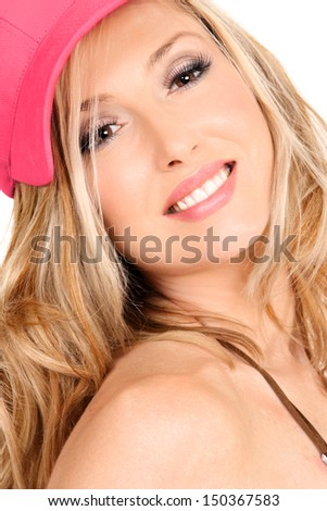 Smiling woman with strong makeup and wavy long blond tousled hair under a pretty coral pink cap. - stock photo
