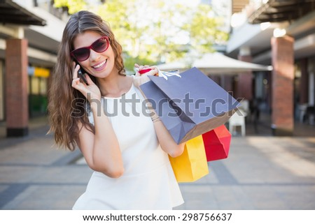 Smiling woman with sunglasses and shopping bags calling at the shopping mall - stock photo