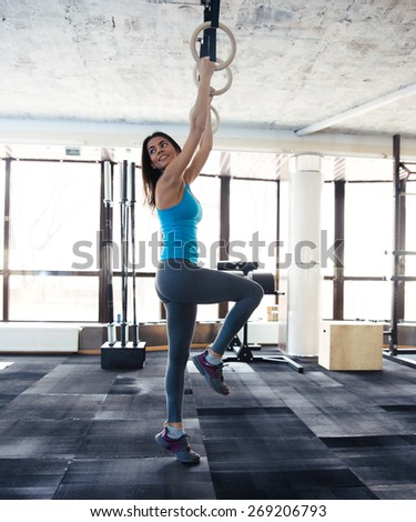 Smiling woman working out on gimnastic rings at gym and looking away - stock photo