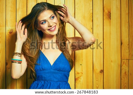 Smiling woman. Young Woman Portrait against Wooden Background. Beautiful smiling girl with long hair.  - stock photo
