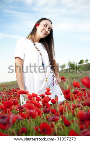 Smiling women in a poppy field - stock photo