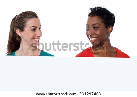 Smiling women looking at each other - stock photo