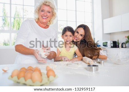 Smiling women of a family baking together in the kitchen - stock photo