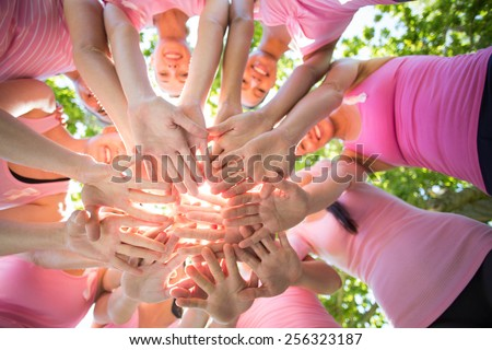 Smiling women organising event for breast cancer awareness on a sunny day - stock photo