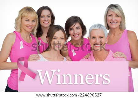 Smiling women posing and wearing pink for breast cancer against pink card - stock photo
