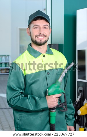 Smiling worker at the gas station, while filling a car - stock photo