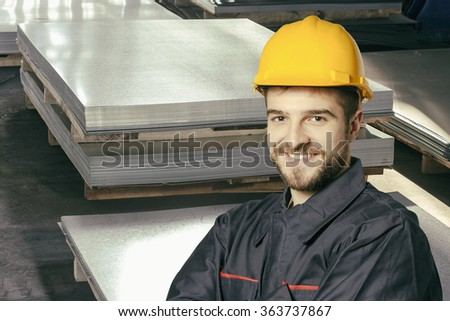 Smiling worker in protective uniform in front of sheet tin metal - toned image, retro film filtered in instagram style - stock photo