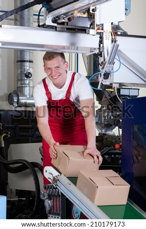 Smiling worker packing boxes on conveyor belt - stock photo