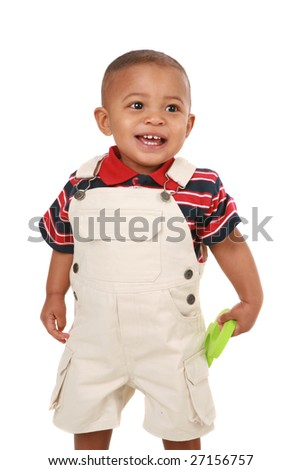 Smiling 1-year old baby boy standing holding toy on isolated background - stock photo