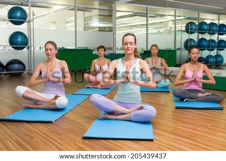 Smiling yoga class in lotus pose in fitness studio at the leisure center - stock photo