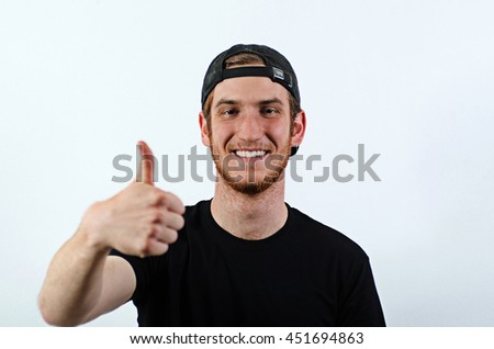 Smiling Young Adult Male in Dark T-Shirt and Baseball Hat Worn Backwards Gesturing, Showing Thumbs Up - stock photo