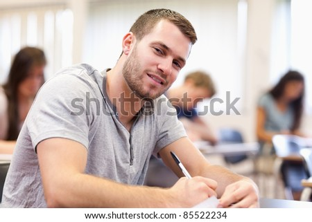 Smiling young adult writing in a classroom - stock photo