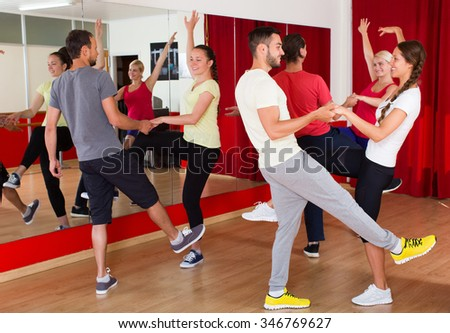Smiling young adults having dance class at studio. Selective focus