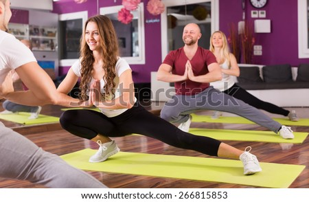 Smiling young adults having group fitness class in sport club - stock photo