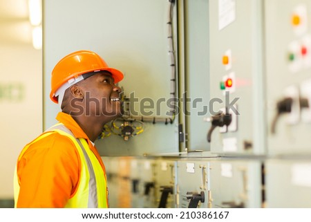 smiling young african american electrician looking at control room - stock photo