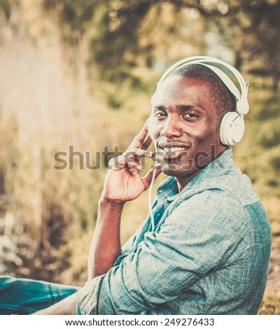 Smiling young african american listens music in a park - stock photo