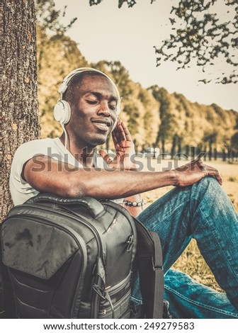 Smiling young african american man listens music in a park - stock photo