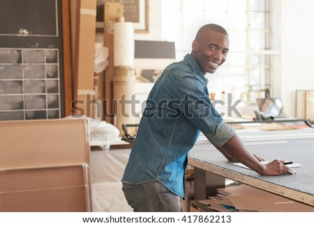 Smiling young African business owner working in his studio - stock photo