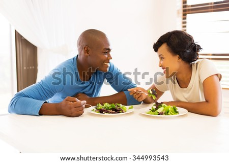 smiling young african couple eating dinner together at home - stock photo
