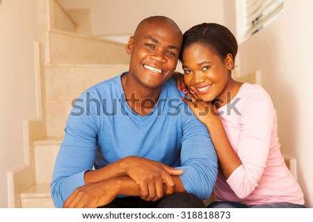 smiling young african couple relaxing at home - stock photo
