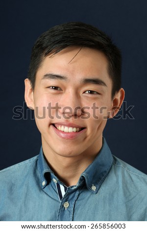Smiling young Asian man looking at camera - stock photo