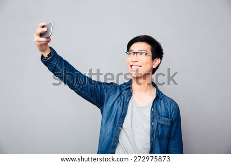 Smiling young asian man making selfie photo on smartphone over gray background - stock photo