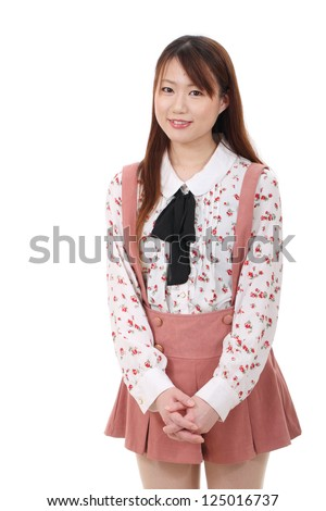 Smiling young asian standing and holding her hands together - stock photo