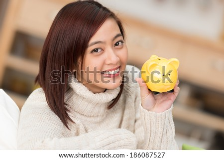 Smiling young Asian woman holding up a cute little yellow piggy bank as she advocates saving for personal goals and retirement - stock photo
