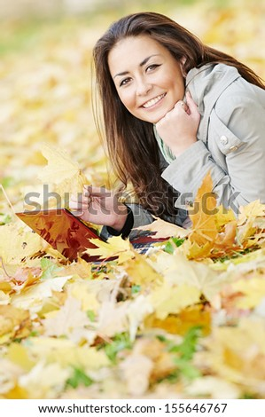 Smiling young attractive woman with laptop computer lying on autumn maple leaves in park at fall outdoors - stock photo