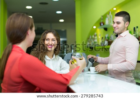 Smiling young bartender and two beautiful women with wine at bar. Focus on girl - stock photo