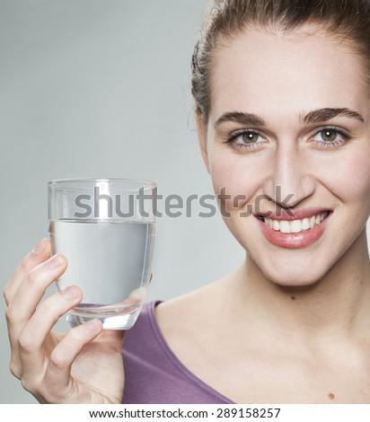 smiling young beautiful woman wearing purple shirt displaying glass of pure tap water - stock photo