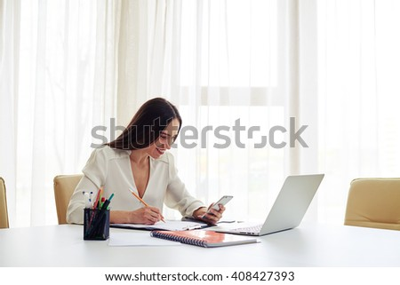 Smiling young beautiful woman working at her smartphone and holds a hand near the head in the modern spacious office - stock photo