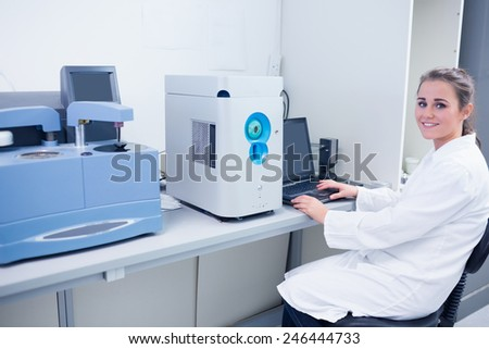 Smiling young biochemist using laptop at her desk in laboratory - stock photo