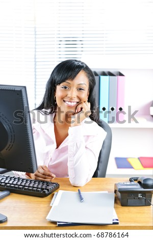 Smiling young black business woman at desk in office - stock photo