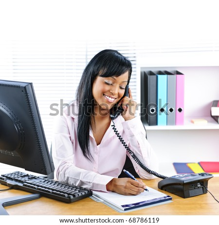 Smiling young black business woman on phone taking notes in office - stock photo