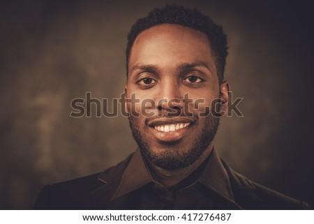Smiling young black man posing on dark background.  - stock photo
