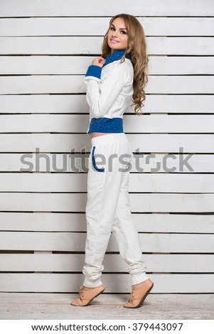 Smiling young blond woman in white and blue clothes posing near wooden wall - stock photo
