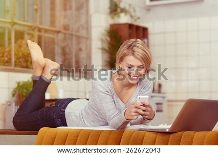 Smiling Young Blond Woman Lying on her Stomach on the Table Behind the Sofa While Using her Phone In front of her Laptop Computer. - stock photo