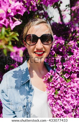 Smiling young blond woman wearing sunglasses and jeans jacket in sun surrounded by purple flower blooms on tree - stock photo