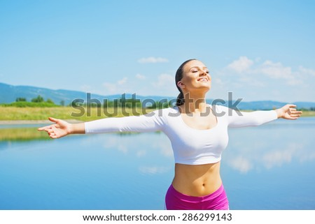 Smiling young blonde Caucasian woman in pink and white sportswear stretching hands feeling free standing by the lake. Fitness girl with hands wide stretched outdoors on sunny summer day. - stock photo