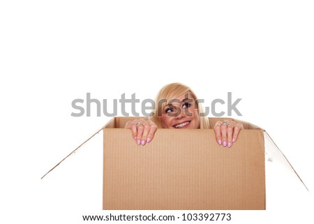 Smiling young blonde emerging from a box isolated on white - stock photo
