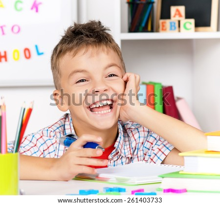 Smiling young boy doing homework at the table - stock photo