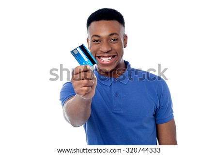 Smiling young boy showing credit card - stock photo