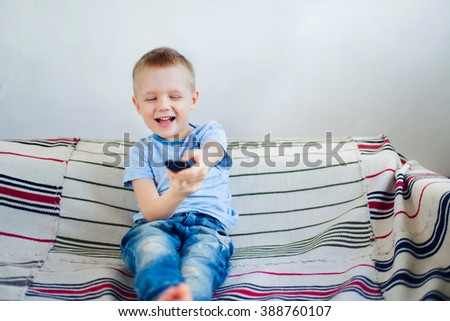 Smiling young boy switching over to another tv channel - stock photo